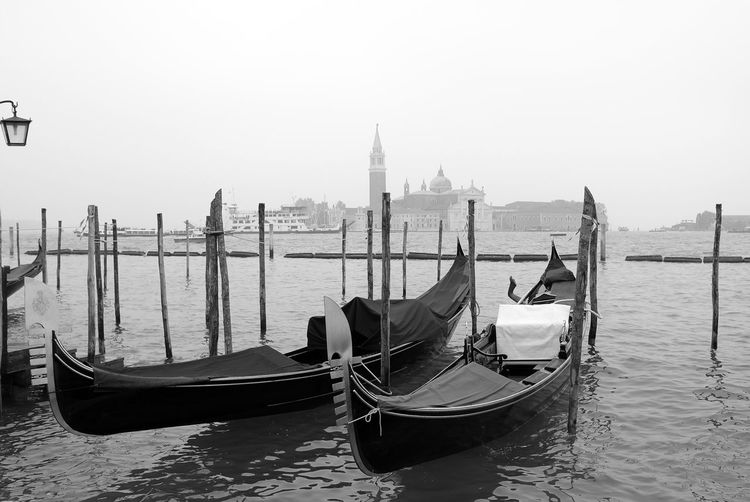 Gondolas moored at grand canal against clear sky