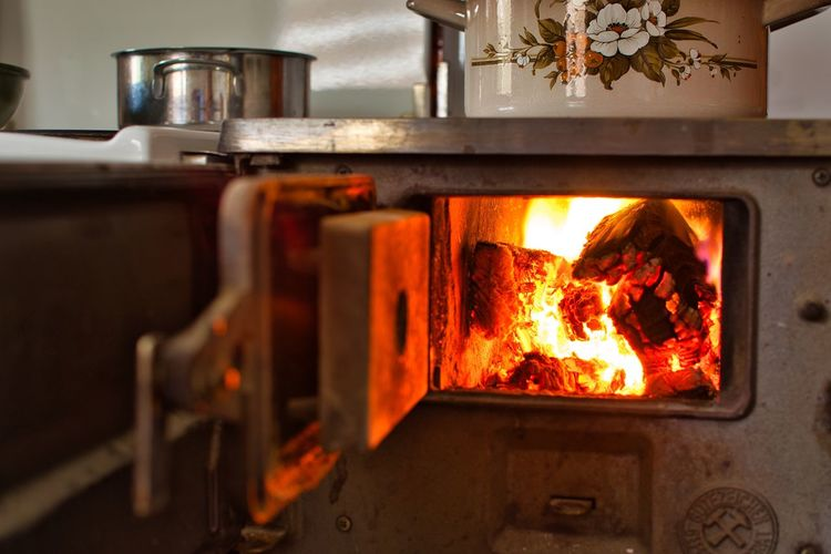 Close-up of fire burning in oven at kitchen
