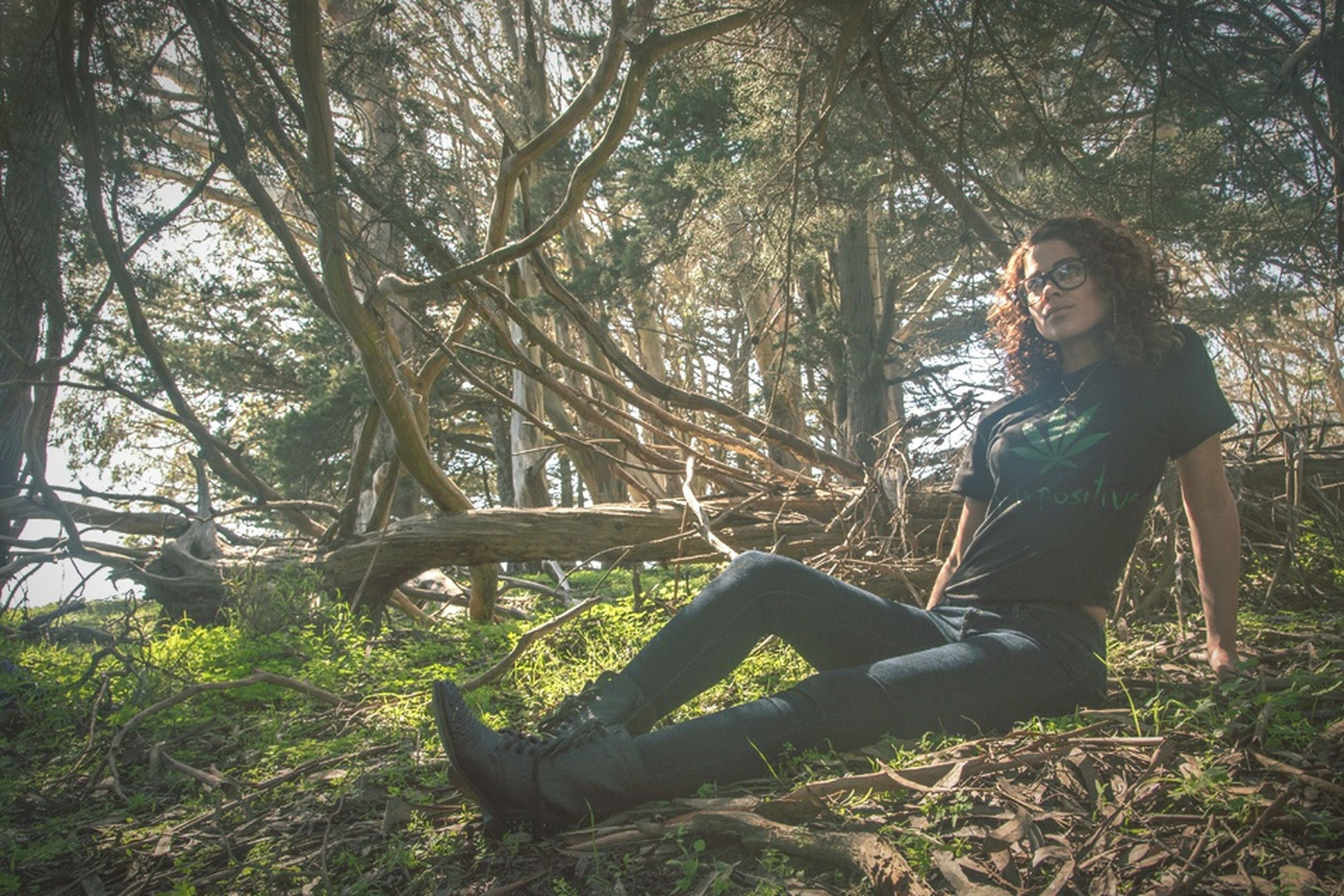 tree, lifestyles, leisure activity, young adult, casual clothing, young women, sitting, person, forest, tree trunk, relaxation, full length, side view, nature, tranquility, standing, growth, three quarter length