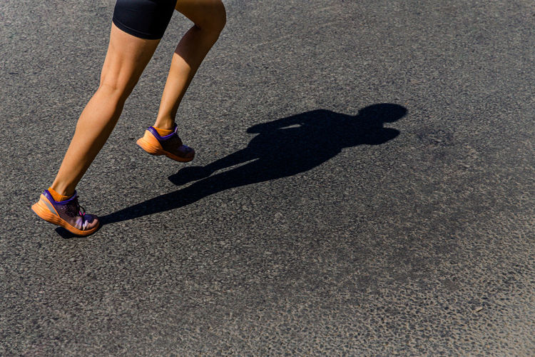 Low section of person running on road