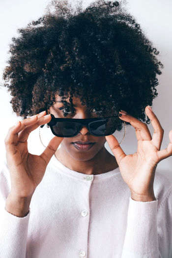 Beautiful black woman with afro hair wearing futuristic video recording glasses