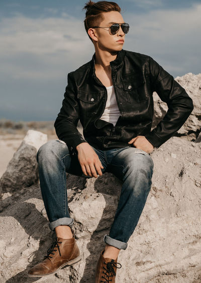 Full Length Of Fashionable Young Man Looking Away While Sitting On Rock