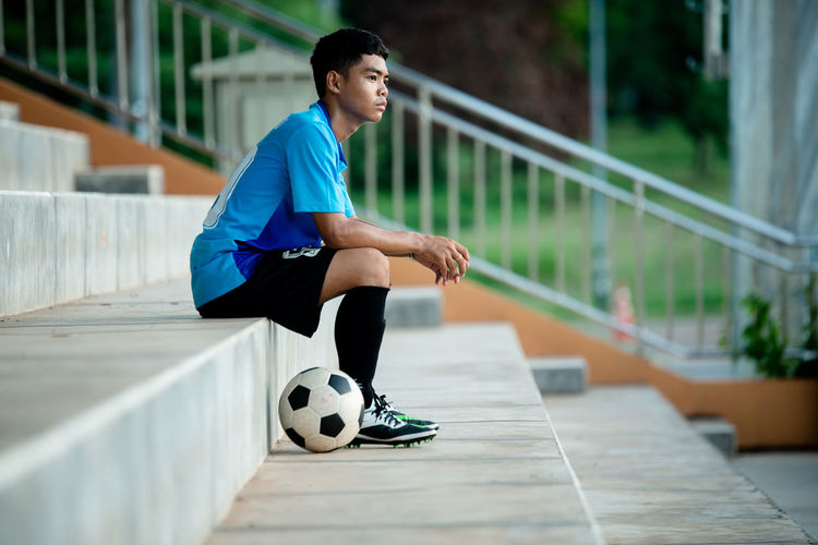 Side view full length of soccer player sitting on steps