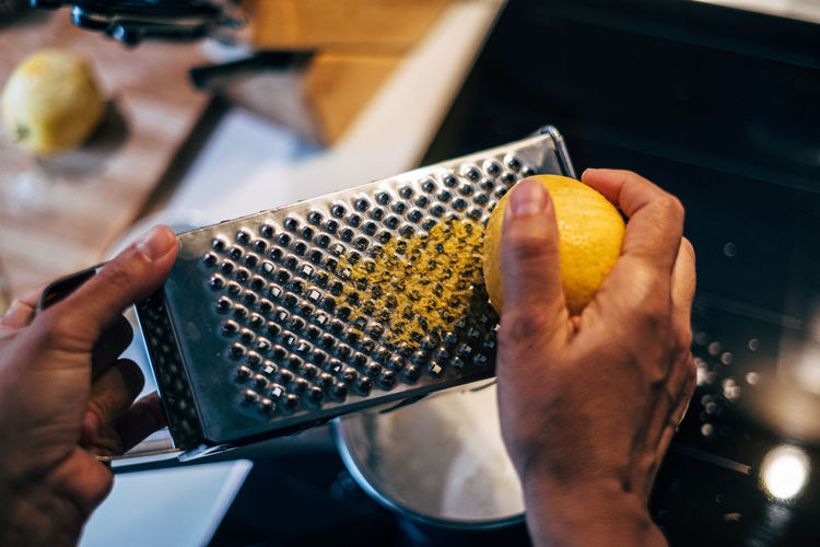 High angle view of human hand grating lemon