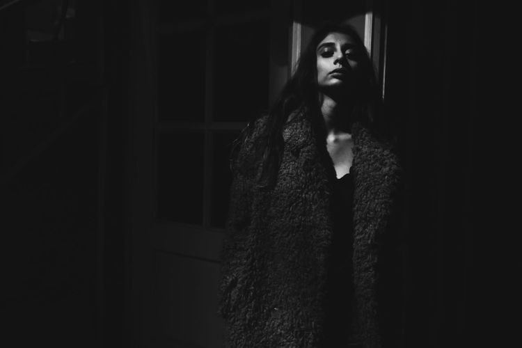 Young woman standing in the dark