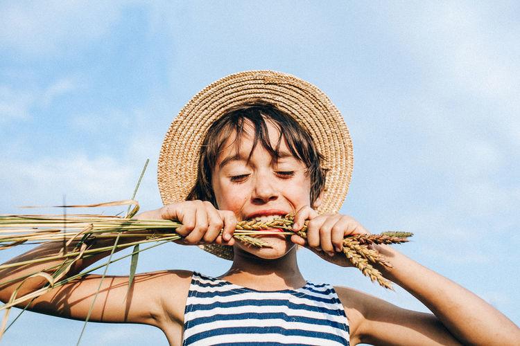 Boy biting crop against sky