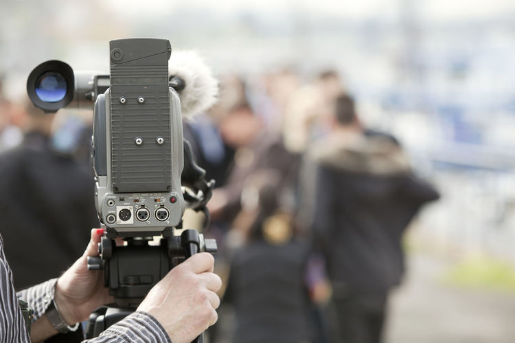 Close-up of cropped cameraman photographing crowd