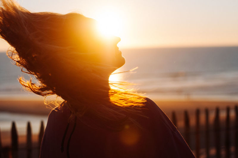 Close-up of woman with tousled hair at beach during sunset