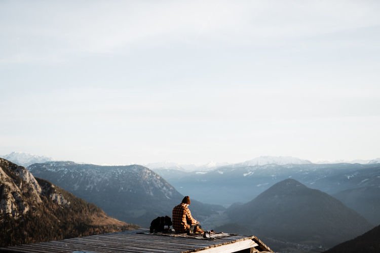 Rear view of man on rock against sky