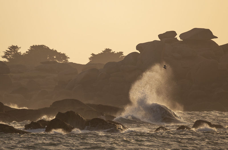 Waves splashing on rocks at shore against clear sky