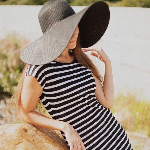 Beautiful woman in striped dress wearing black hat
