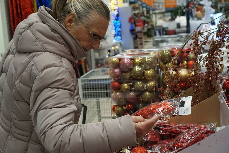 Senior woman holding decoration in plastic at store