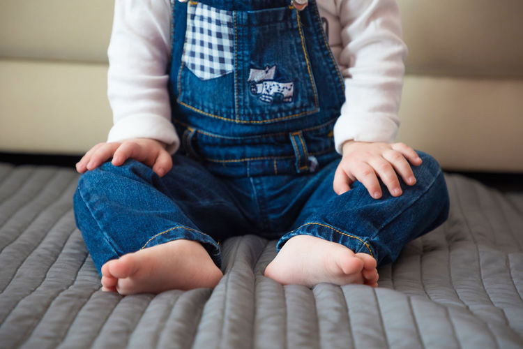 Jeans Baby Baby Boy Babyhood barefoot Bed Bonding Boys Casual Clothing Childhood Comfortable Cute Day Domestic Life Front View Home Interior Human Body Part Human Leg Indoors  Jeans Leisure Activity Lifestyles Low Section One Person Real People Relaxation Sitting Toddler