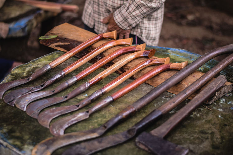 Midsection of man standing by old work tools at market stall