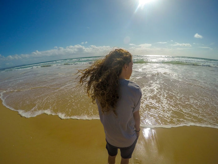 The beach Childhood Child Long Hair Curly Hair Brown Windy Clouds And Sky Sunny Colour Blue Sky Horizon Brown Hair Water Sea Beach Standing Motion Wave Young Women Summer Sand Children