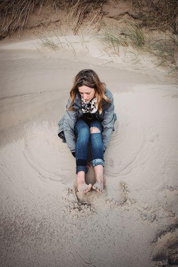Full length portrait of woman sitting on sand