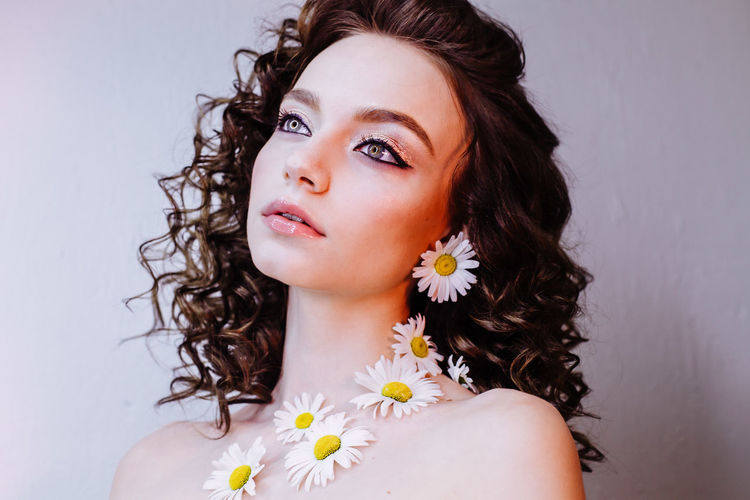 Close-up of beautiful young woman wearing flowers and make-up against wall