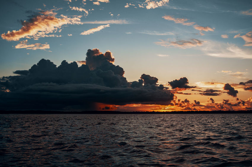 Amazonian sunset. Amazon Amazonas Rainforest Jungle South America Latin America Sky Cloud - Sky Sunset Water Reflection Reflections In The Water Rippled Sun Moody Boat Outdoors Nature Tranquility Non-urban Scene No People Orange Color Dramatic Sky Idyllic Horizon Over Water