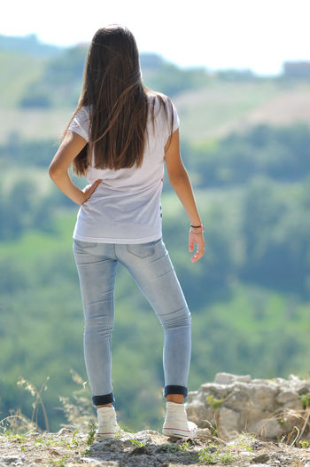 Rear view of teenage girl standing on land