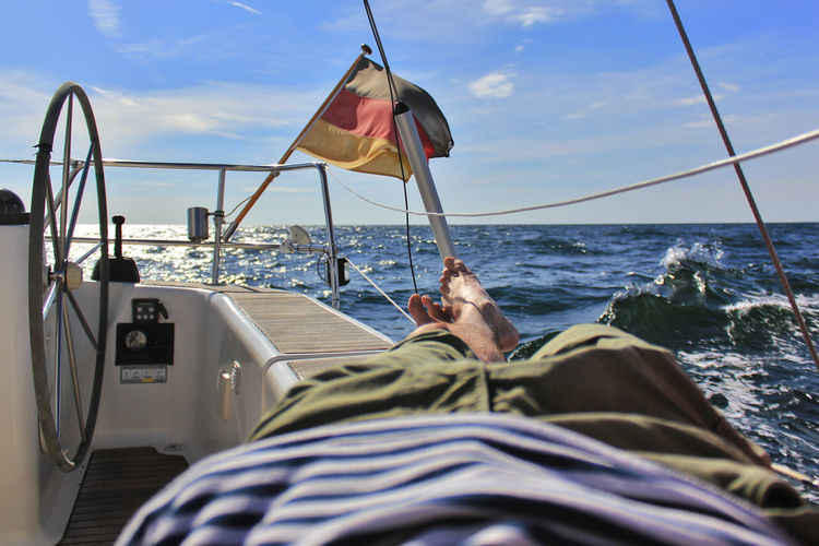 Low section of man relaxing on boat in sea against sky