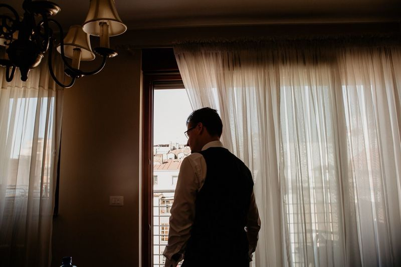 Rear view of businessman looking through window at home