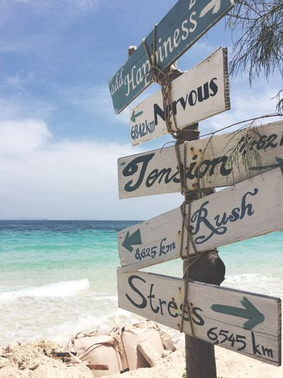 Directional Signs At Sea Shore Against Sky