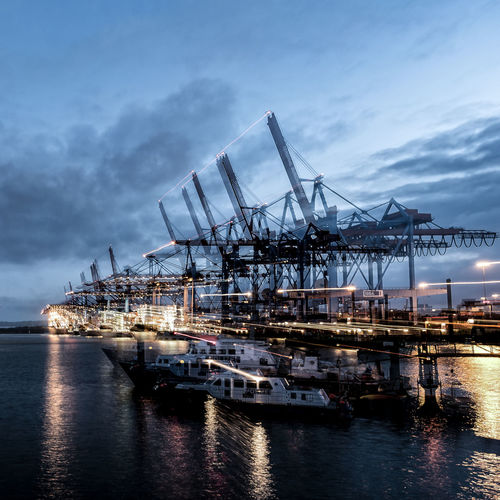Cranes at commercial dock against sky at night