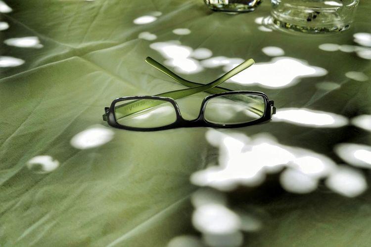 High angle view of eyeglasses on glass