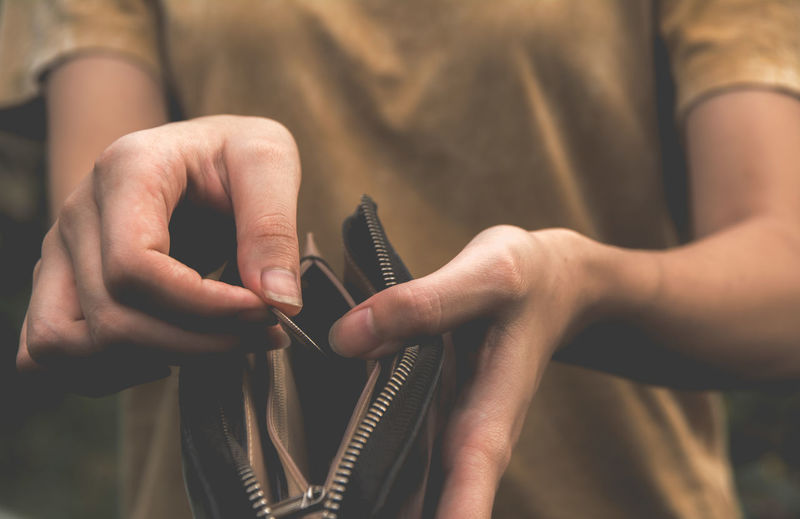 Midsection of woman holding purse and coin
