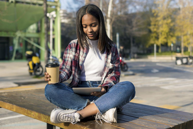 Young beautiful african american woman sitting outdoors in the city with a tablet pc while holding a take away coffee in a sunny day One Person Casual Clothing Sitting Technology Young Adult Wireless Technology Real People Adult Lifestyles Communication Hair Connection Young Women Leisure Activity Front View Focus On Foreground Day Holding Full Length Food And Drink Hairstyle Jeans Beautiful Woman Outdoors Take Away Relaxing Sitting Laugh Laughing Sunny Daylight