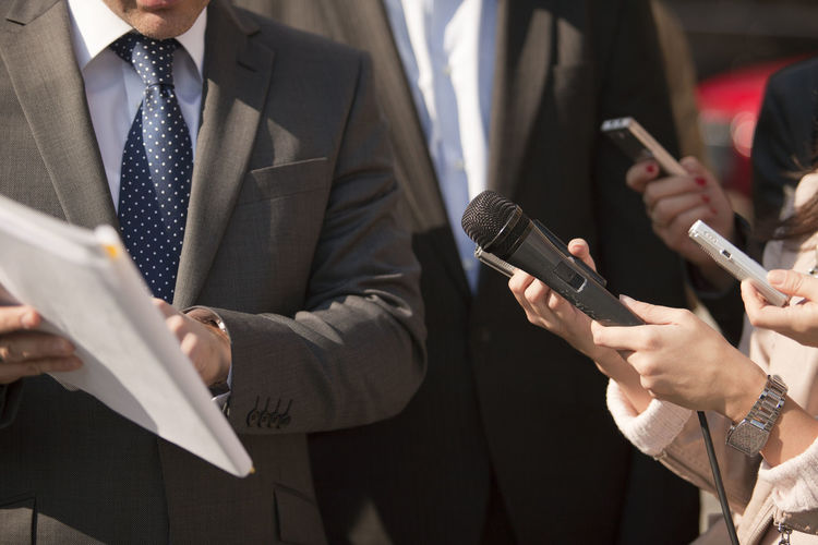 Midsection of journalist holding microphone in front of businessman