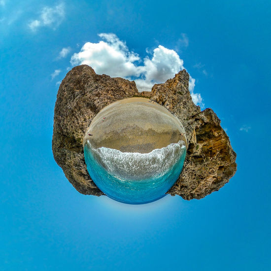 Low angle view of rock on sea against sky