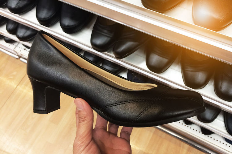 High angle view of hand holding shoe in store