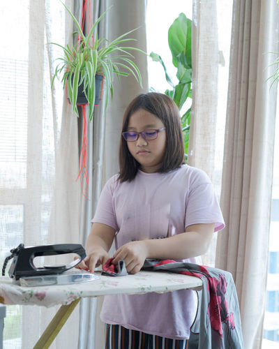 Young woman wearing eyeglasses on table