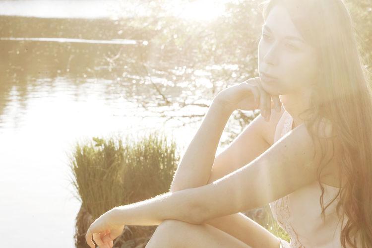 Thoughtful Beautiful Woman Sitting At Lakeshore