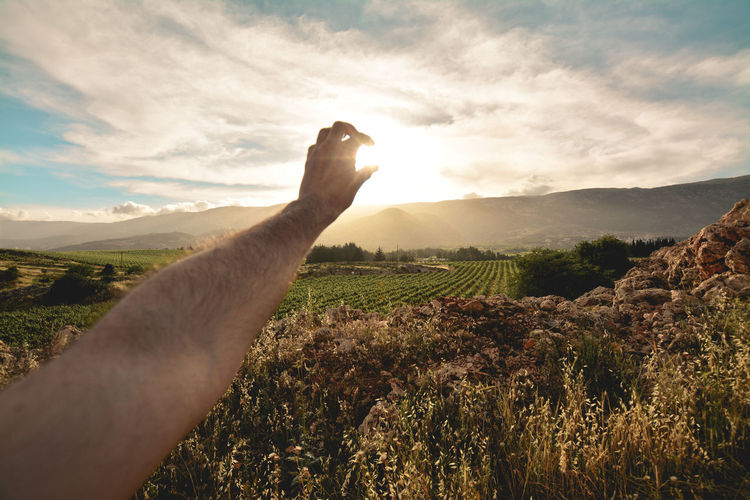 Optical illusion of man hand holding sun against sky
