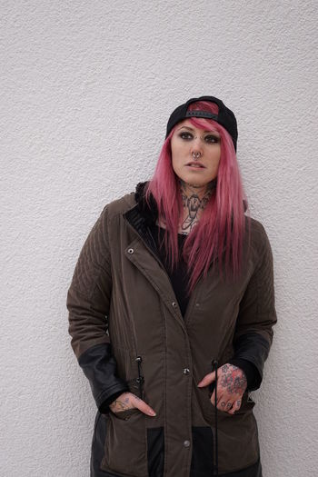 Young Woman With Pink Hair Standing Against White Wall