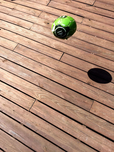 that old ball sails from a hot deck leaving nothing but sound and shadow. Arrangement Ball BOUNCE Brown Circle Deck Diagonal Green Color High Angle View Lines Movement Pattern Photography In Motion Shadow Soccer Speed Sport Sunlight And Shadow Sunny Wood Wood - Material Wooden Live For The Story