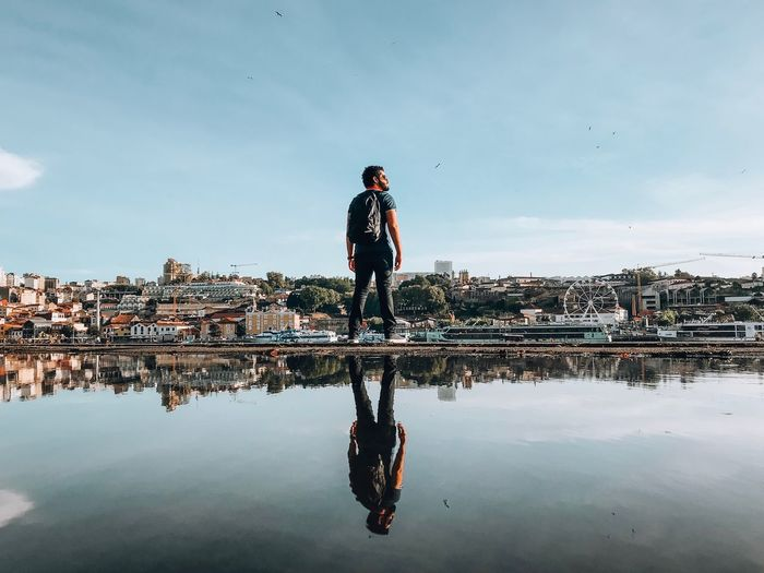 Man standing in city against sky