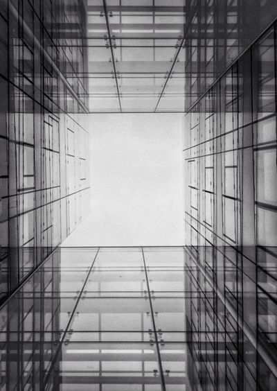 Directly below shot of glass building against sky