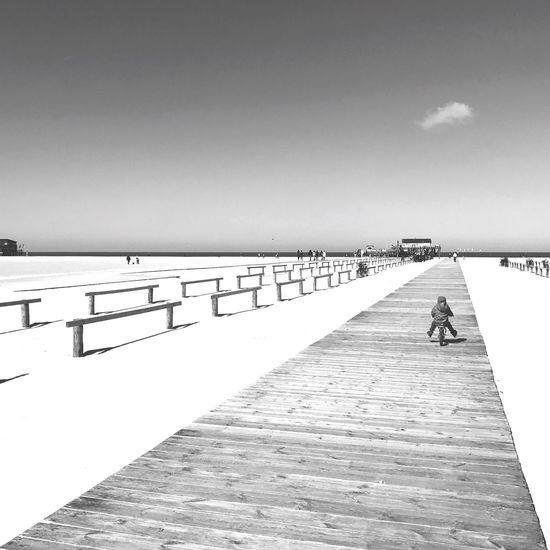 The Great Outdoors - 2017 EyeEm Awards Pier Copy Space Full Length Day Walking Outdoors Sea Sunlight Sky Real People Beach Nature Clear Sky Tranquility One Person Men Water Horizon Over Water Beauty In Nature People BeachBnwlovers Bnw_collection