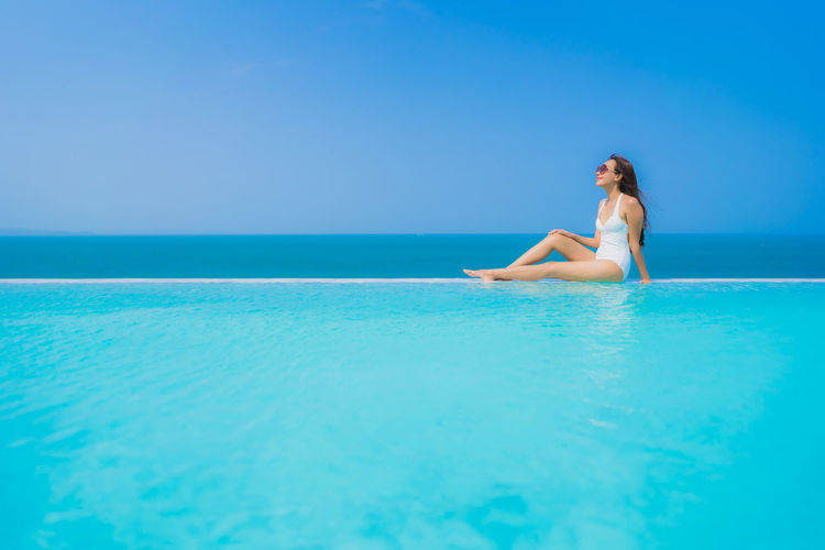 Young woman relaxing at infinity pool against sea
