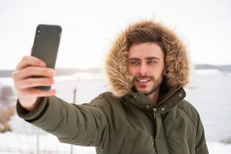 Smiling young man taking selfie standing outdoors