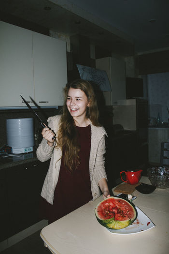 Smiling woman looking at knife while standing by watermelon at home