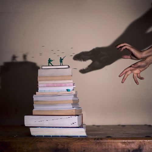Cropped Image Of Hands Making Dinosaur Shadow Attacking On Soldier Figurines On Books