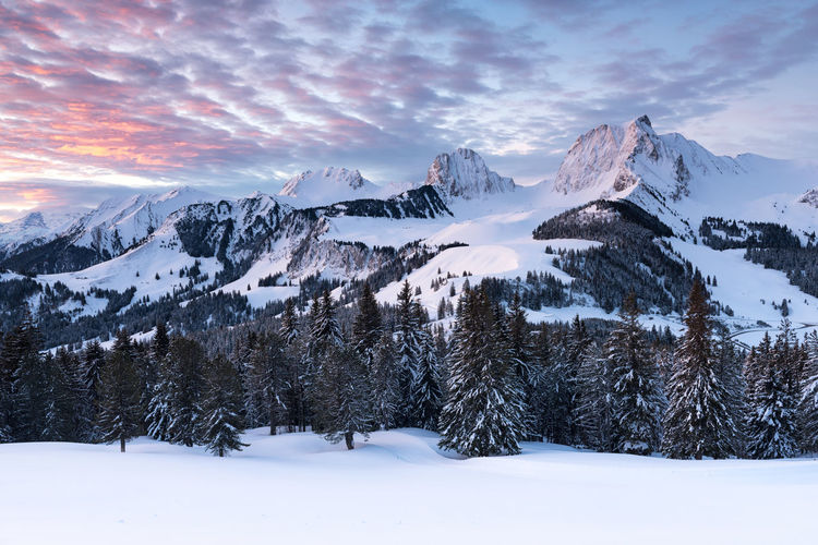 Scenic View Of Snow Covered Landscape And Mountains Against Sky During Sunset