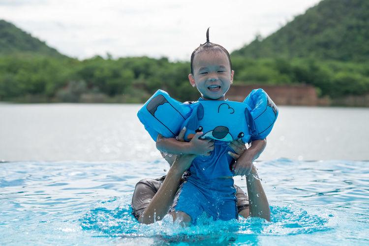 Woman Lifting Boy Wearing Water Wings In Swimming Pool
