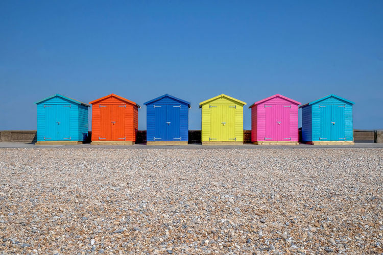 Colorful beach huts against clear blue sky