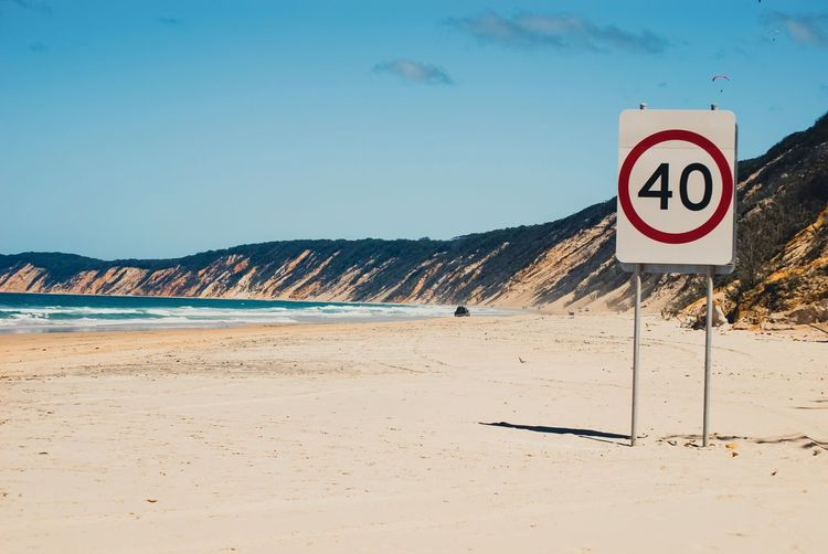 Speed limit sign at beach against sky