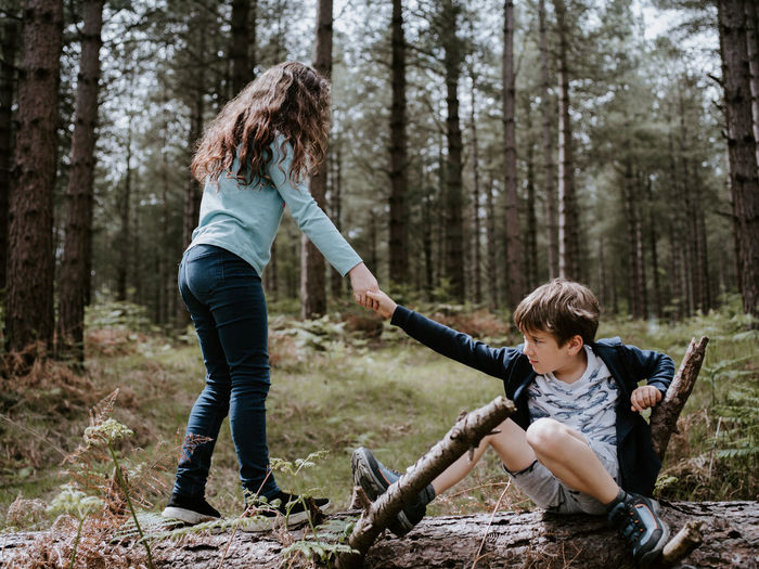 Full length of sister assisting brother in forest
